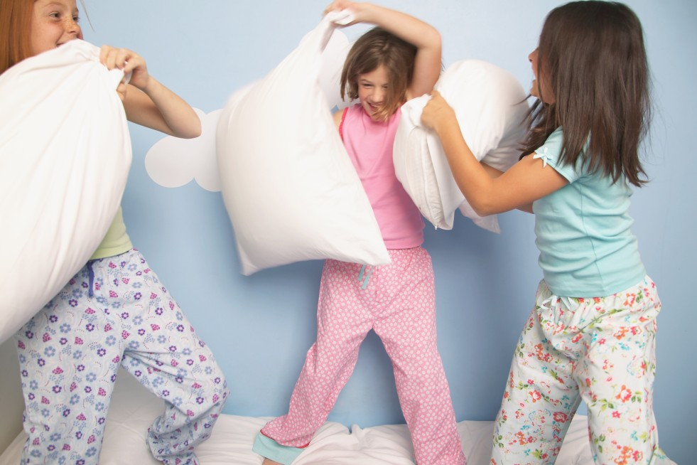 Three girls (8-10) having pillow fight on bed